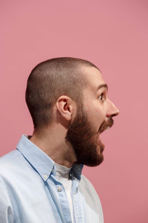 Le jeune homme étonnant émotif criant sur le fond rose de studio photographie stock libre de droits