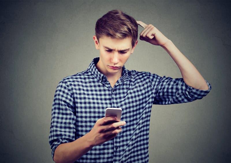 Le jeune homme a abasourdi au sujet de ce qu'il voit sur le téléphone portable, recherchant la solution photo stock
