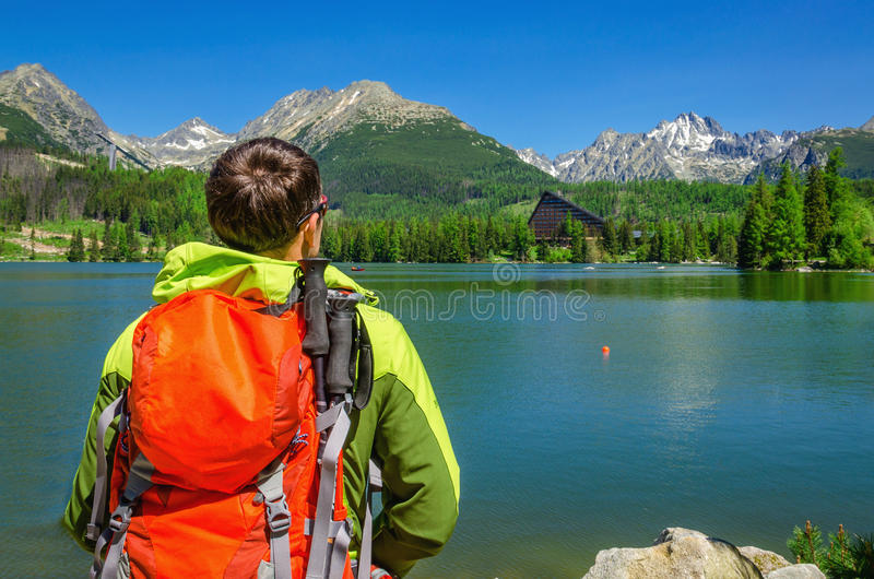 Le jeune homme admire de hautes montagnes et lac Slovaquie photo stock
