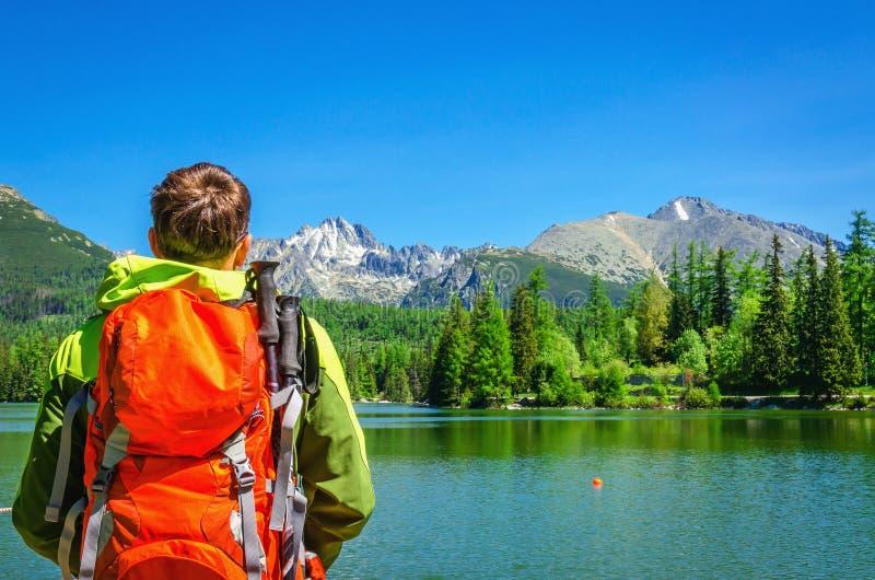 Le jeune homme admire le lac Strbske Pleso de montagne photos stock