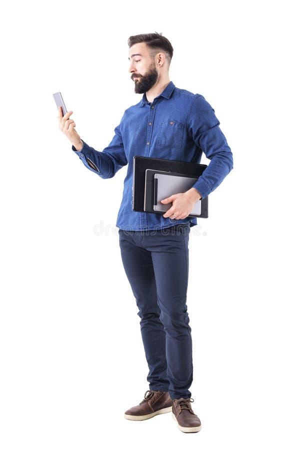 Le jeune homme adulte d'affaires tenant l'ordinateur portable et le comprimé sous le bras vérifiant le téléphone portable signale photo stock