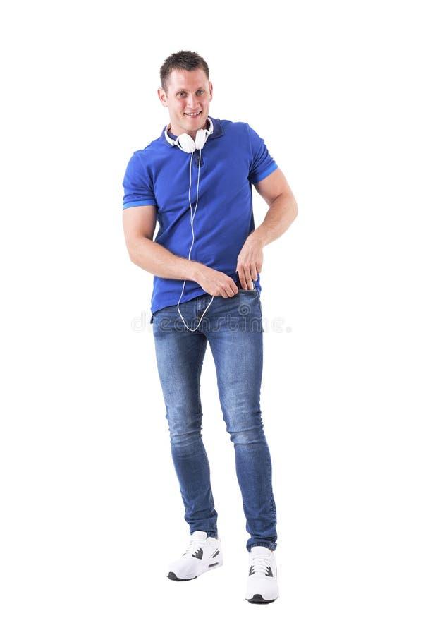 Le jeune homme adulte heureux a mis le smartphone dans la poche avec des écouteurs autour du cou regardant l'appareil-photo image stock