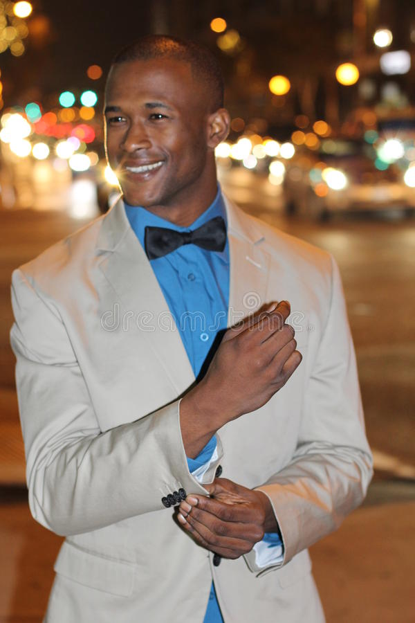Le jeune homme africain attirant la nuit avec la ville s'allume derrière lui, la veste élégante de port de costume et le bowtie images stock