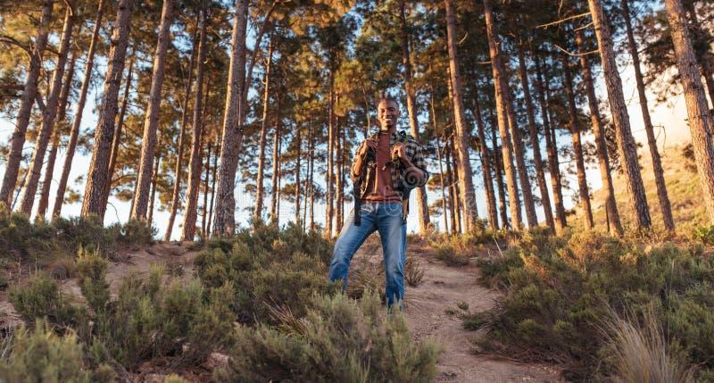 Le jeune homme africain de sourire se tenant sur une forêt traînent photo libre de droits
