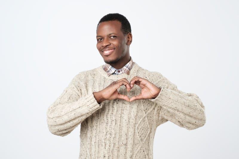 le jeune homme africain fait la forme de coeur de main utilisant le fond blanc d'isolement par doigts Émotions humaines positives image stock