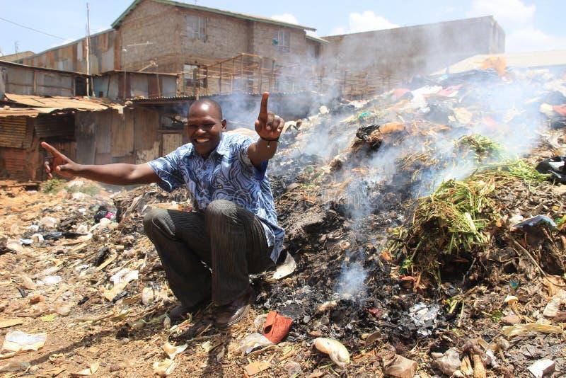 Le jeune homme africain s'assied et sourit sur une montagne des déchets photo stock