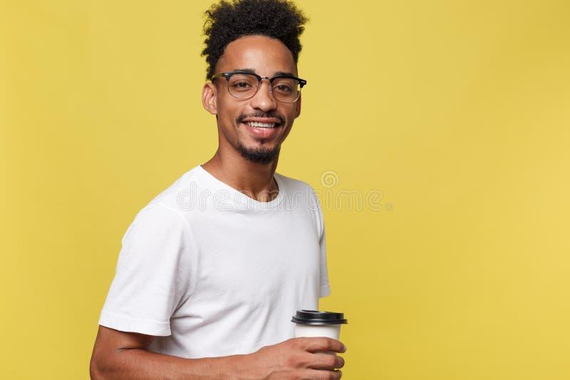 Le jeune homme afro-américain élégant tenant la tasse de emportent le café d'isolement au-dessus du fond jaune photographie stock
