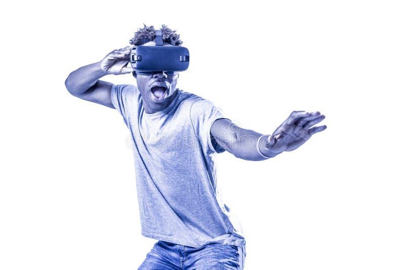 Le jeune homme afro-américain enthousiaste actif appréciant jouer heureux avec le dispositif visuel de réalité virtuelle des lune photo libre de droits