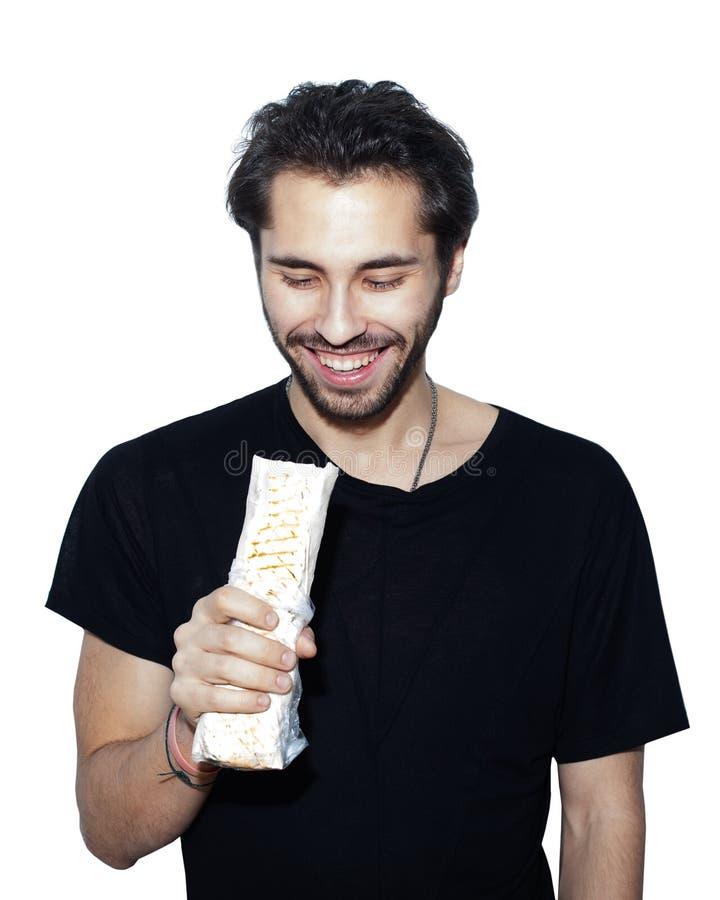 Le jeune homme arabe bel mange avec le chiche-kebab Shawarma de Donner de plaisir Isolement sur un fond blanc photo stock
