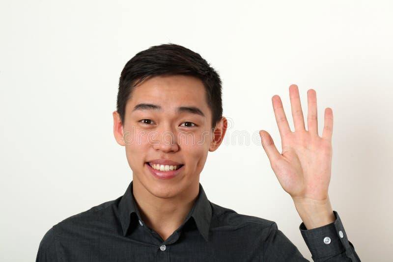 Le jeune homme asiatique de sourire donnant l'arrêt signent et regarder est venu photo stock