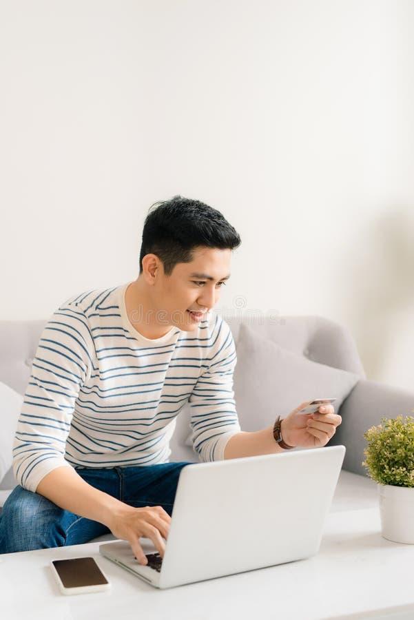 Le jeune homme asiatique effectuent le paiement en ligne avec l'ordinateur portable et la carte de crédit photo stock