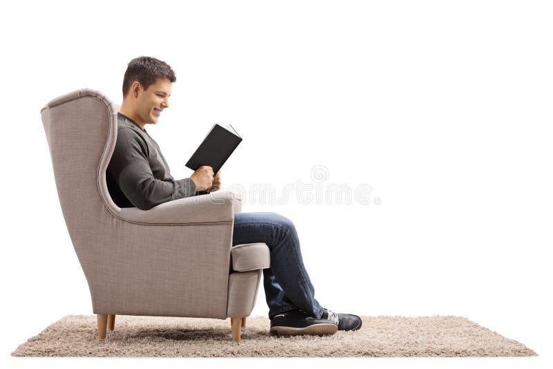 Le jeune homme a assis dans un fauteuil lisant un livre images stock