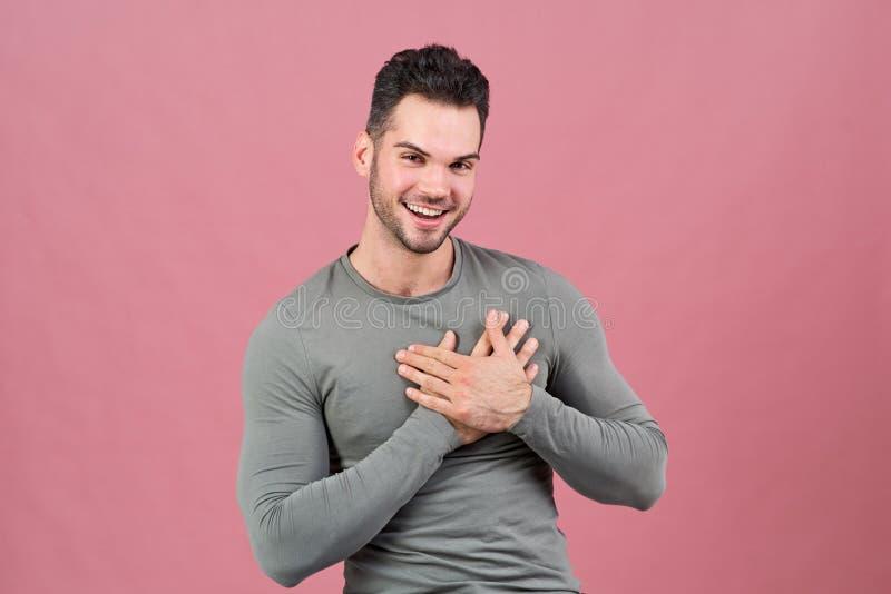 Le jeune homme attirant de la construction sportive sourit heureusement et tient ses mains près de son coeur Le concept de l'amou photos stock