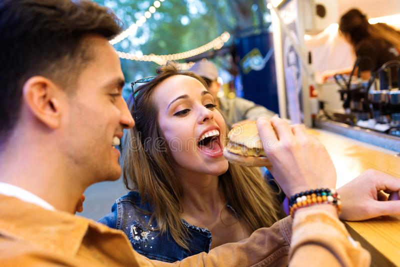 Le jeune homme attirant donnant l'hamburger à sa belle amie mangent dedans le marché de la rue images libres de droits