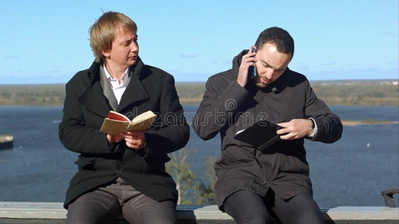 Le jeune homme au téléphone touche au withbook d'homme photographie stock
