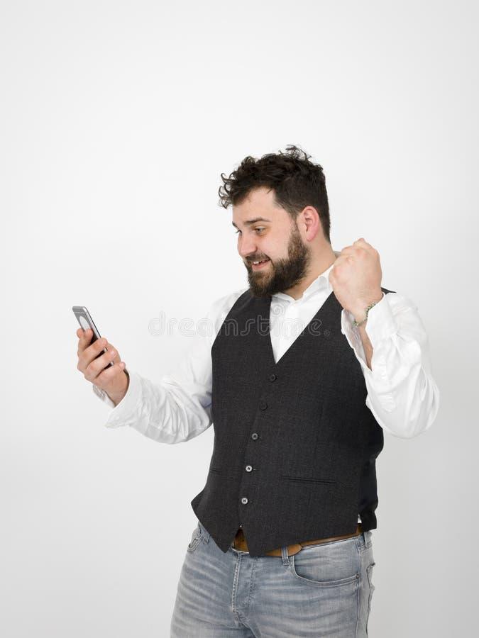 Le jeune homme avec la barbe noire est posant et regardant son smartphone devant le fond blanc avec diff?rentes ?motions photo libre de droits