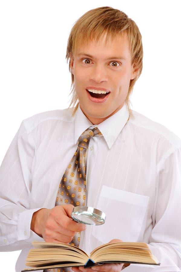 Le jeune homme avec la loupe est étonné par le livre affiché photo libre de droits