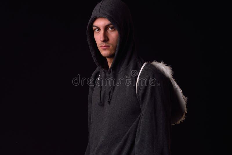 Le jeune homme avec le hoodie noir et le blanc a fait varier le pas des ailes derrière photo libre de droits