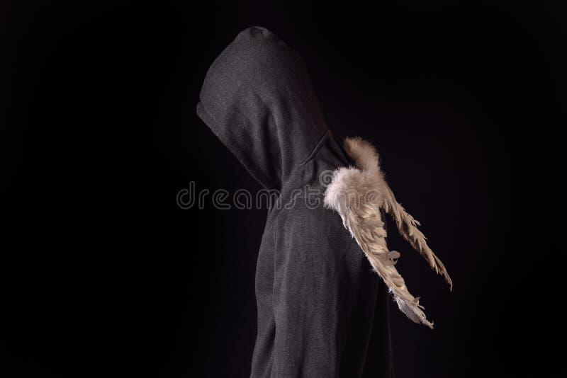 Le jeune homme avec le hoodie noir et le blanc a fait varier le pas des ailes derrière photographie stock libre de droits