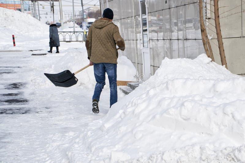 Le jeune homme avec une pelle nettoie une rue de ville après des chutes de neige d'un ressort photos stock