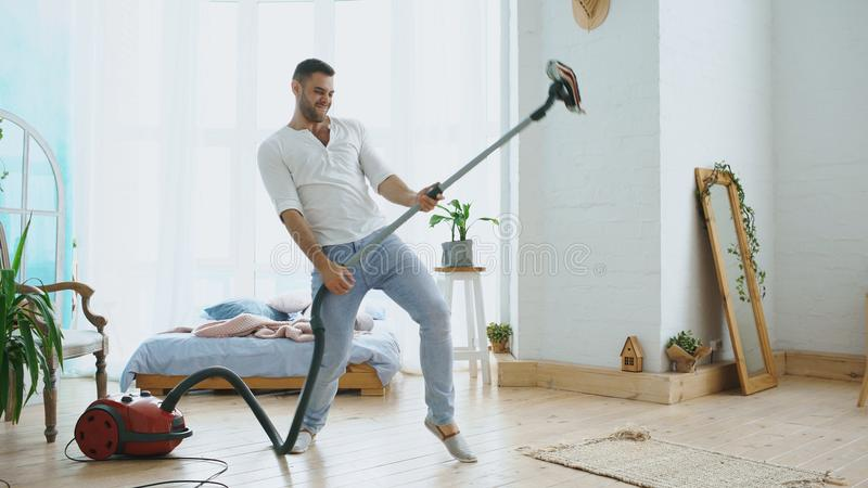 Le jeune homme ayant la maison de nettoyage d'amusement avec la danse d'aspirateur aiment le guitariste images stock