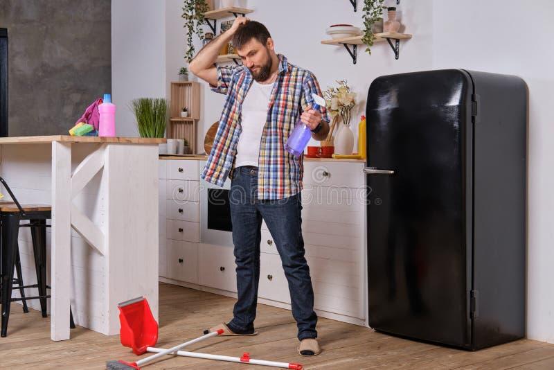 Le jeune homme barbu bel dans la cuisine, chemise à carreaux de port, essaye de traiter une pelle à poussière et un balai photos libres de droits