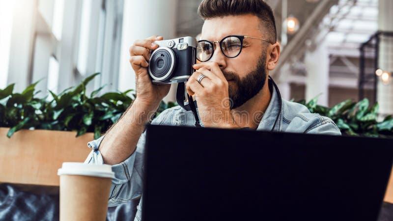 Le jeune homme barbu s'assied dans le café à la table devant l'ordinateur portable et prend la photo instantanée sur l'appareil-p photographie stock