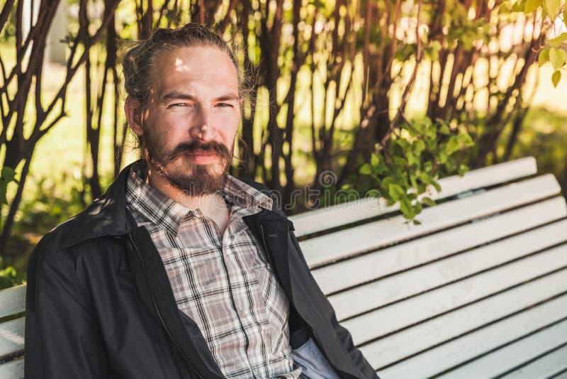 Le jeune homme barbu s'assied sur un banc photos libres de droits