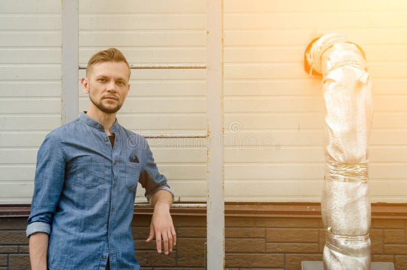 Le jeune homme barbu s?rieux dans la chemise de denim se tient pr?s du mur du b?timent industriel pr?s de l'?chelle et regarde di image libre de droits