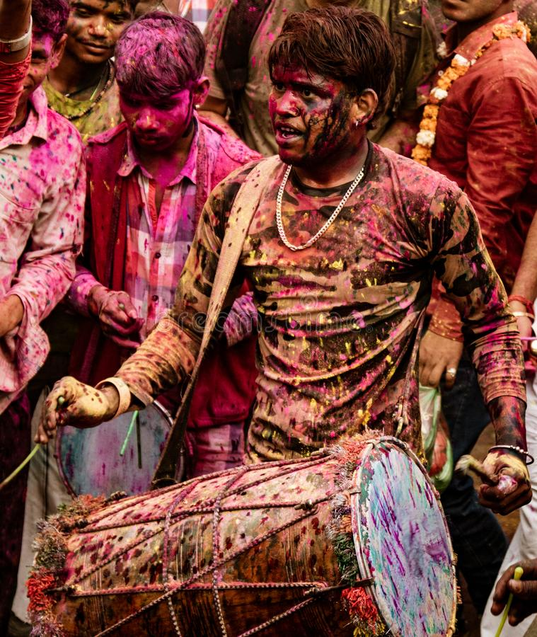 Le jeune homme bat le tambour pour fournir la musique pour le festival de Holi dans l'Inde image stock