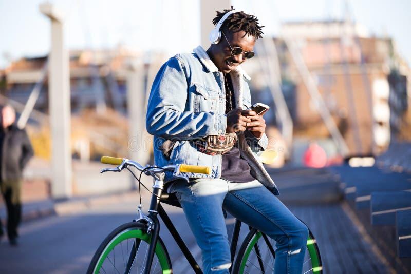 Le jeune homme beau à l'aide du téléphone portable et la vitesse fixe vont à vélo dans la rue photo libre de droits
