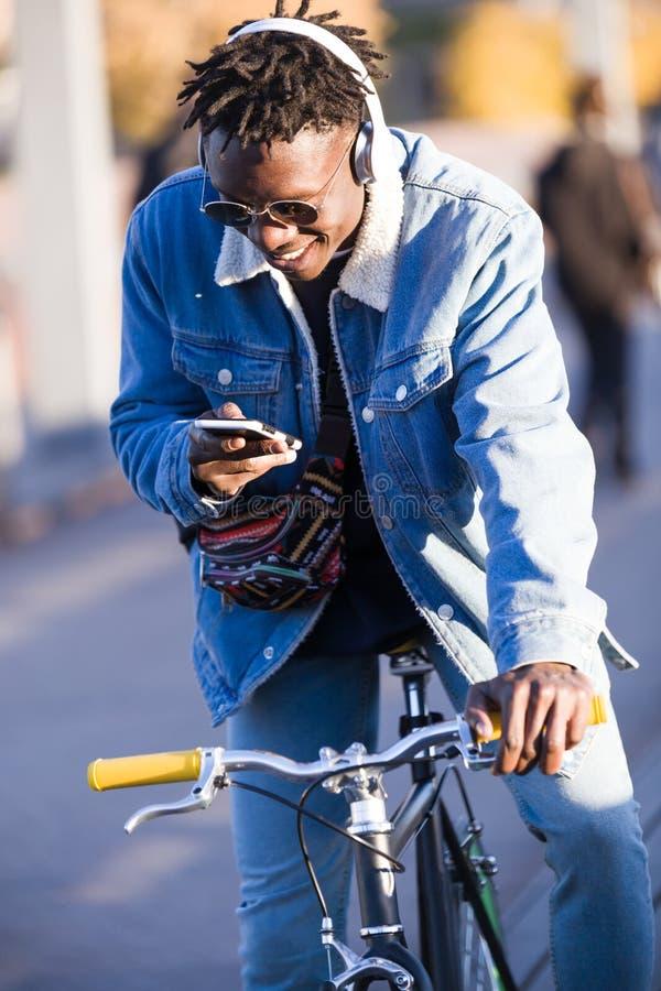 Le jeune homme beau à l'aide du téléphone portable et la vitesse fixe vont à vélo dans la rue photos stock