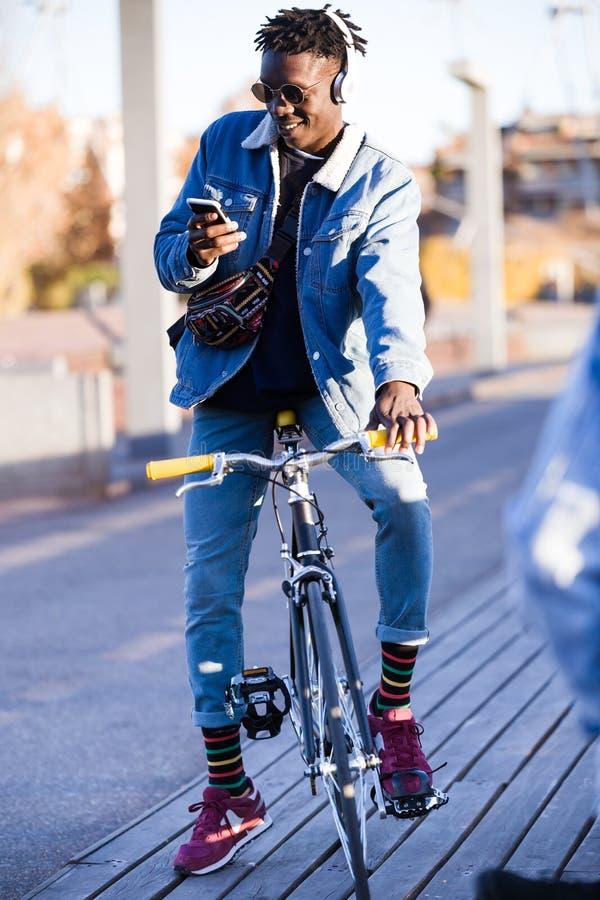 Le jeune homme beau à l'aide du téléphone portable et la vitesse fixe vont à vélo dans la rue image libre de droits