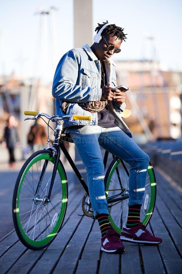 Le jeune homme beau à l'aide du téléphone portable et la vitesse fixe vont à vélo dans la rue photos libres de droits