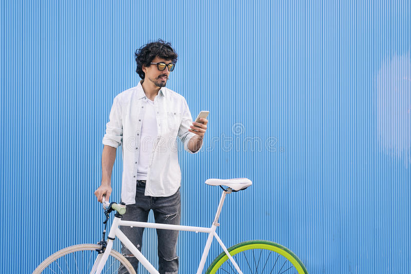 Le jeune homme beau avec le téléphone portable et la vitesse fixe vont à vélo photo libre de droits