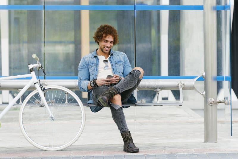 Le jeune homme beau avec le téléphone portable et la vitesse fixe vont à vélo photographie stock libre de droits