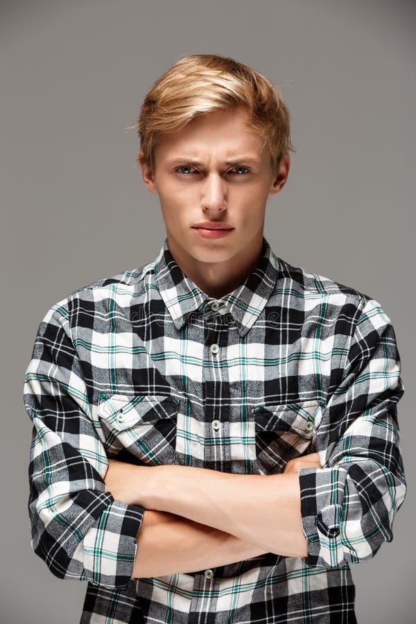 Le jeune homme beau blond fâché utilisant la chemise de plaid occasionnelle avec des mains a croisé sur le coffre regardant l'app images stock