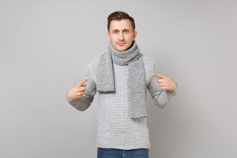 Le jeune homme beau dans le chandail gris, écharpe dirigeant des index sur se a isolé sur le fond gris de mur Sain photos stock