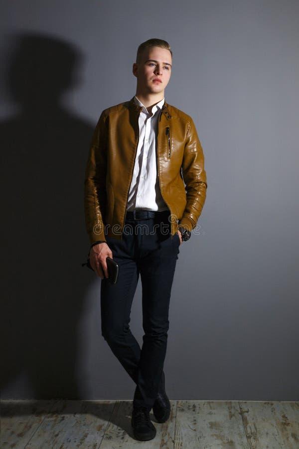 Le jeune homme beau dans la veste en cuir pose avec une bourse photos stock