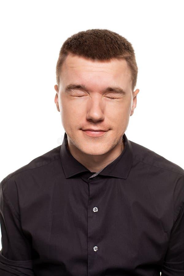 Le jeune homme beau dans une chemise noire fait des visages, tout en se tenant d'isolement sur un fond blanc photo stock