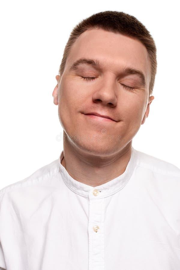 Le jeune homme beau de charme dans une chemise blanche fait des visages, tout en se tenant d'isolement sur un fond blanc photos stock