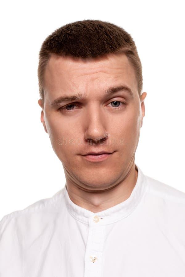 Le jeune homme beau de charme dans une chemise blanche fait des visages, tout en se tenant d'isolement sur un fond blanc photos libres de droits