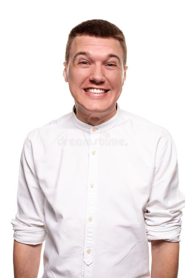 Le jeune homme beau de charme dans une chemise blanche fait des visages, tout en se tenant d'isolement sur un fond blanc image stock