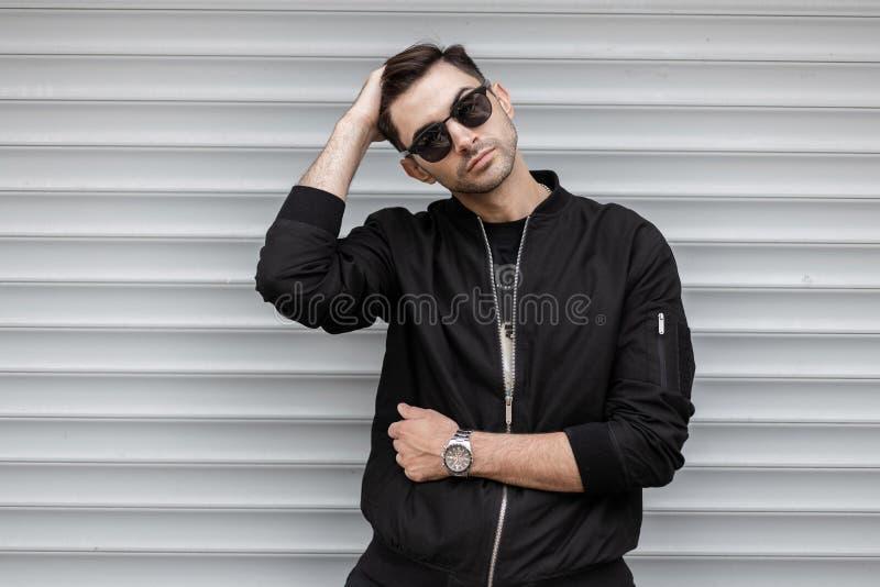 Le jeune homme beau de hippie dans une veste noire à la mode dans des lunettes de soleil élégantes pose dehors près d'un mur mode photos libres de droits