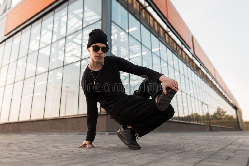 Le jeune homme beau moderne de hippie dans un chapeau tricoté dans des vêtements noirs élégants dans les lunettes de soleil à la  images libres de droits