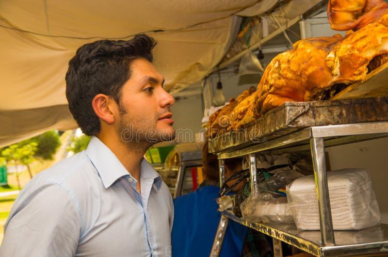 Le jeune homme beau observant un hornado délicieux a rôti le porc, nourriture andine typique traditionnelle d'ecuadorian photos stock