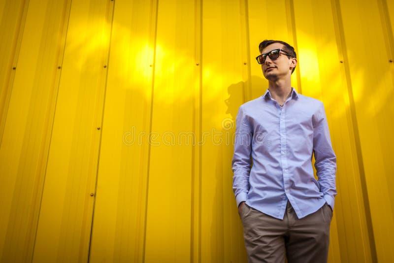 Le jeune homme bel dans des lunettes de soleil se tient contre le mur jaune attendant dehors Équipement élégant d'été images stock
