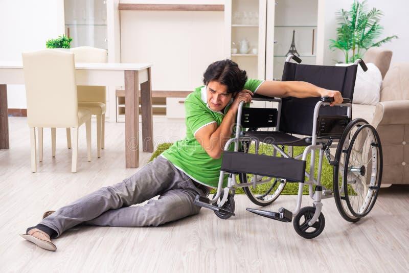 Le jeune homme bel dans le fauteuil roulant ? la maison photos stock