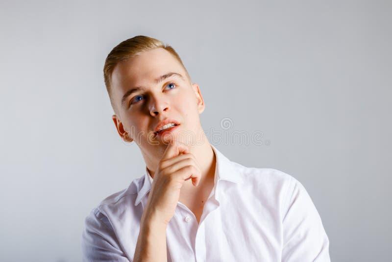 Le jeune homme bel dans la chemise blanche touche son menton photos libres de droits