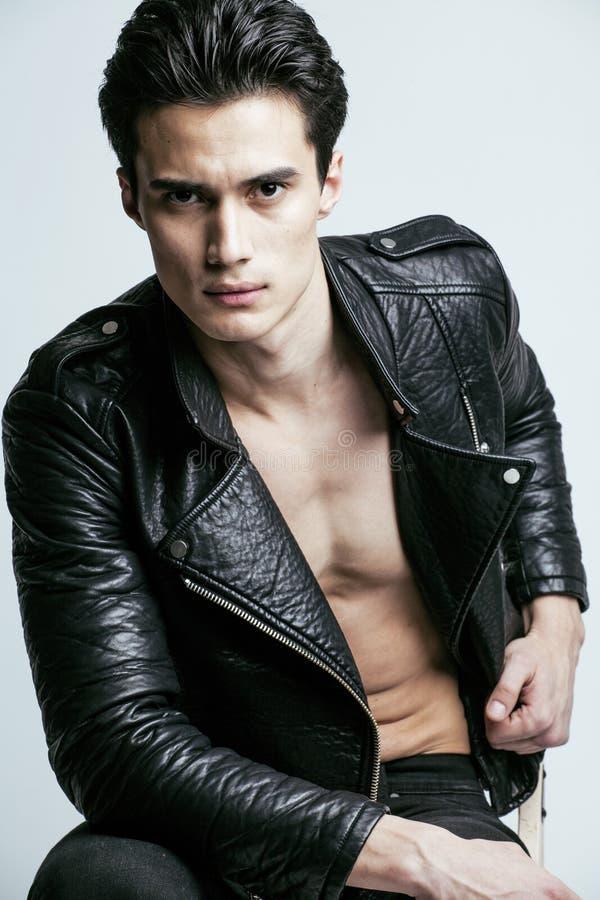 Le jeune homme bel, garnissent en cuir mis sur cric sur le torse nu, pose émotive, fond blanc, type moderne, personnes de mode de photo libre de droits